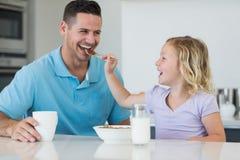 对父亲的女儿供给谷物食品在桌上 免版税库存照片