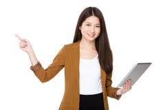 对片剂个人计算机的亚洲年轻女实业家用途和手指指向  图库摄影