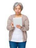 对片剂的亚洲老妇人用途 免版税库存图片