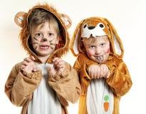 对狮子和兔宝宝服装的男孩  免版税库存照片