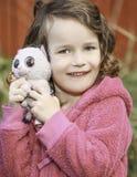 对玩具佩带负的小女婴桃红色在秋天 免版税图库摄影