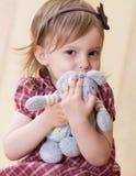 对玩具的怀里钩子女孩小的一只兔子s 免版税库存图片