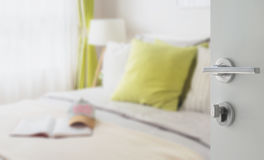 对现代卧室的被打开的白色门有绿色枕头的 库存图片