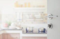 对现代厨房内部的被打开的白色门 免版税库存图片