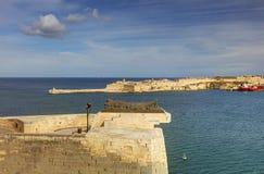 对瓦莱塔市港口的入口在马耳他,有沿海岸线和灯塔的许多历史建筑的 免版税库存图片