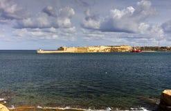 对瓦莱塔市港口的入口在马耳他,有沿海岸线和灯塔的许多历史建筑的 免版税库存照片
