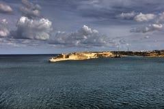 对瓦莱塔市港口的入口在马耳他,有沿海岸线和灯塔的许多历史建筑的 免版税图库摄影