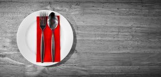 对生来有福和叉子在一块红色餐巾灰色表面上 库存照片