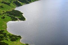 对用草和被包围的绿色土地的鸟瞰图包括的湖 免版税库存照片