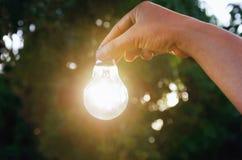 对电灯泡概念负的想法手太阳能量 图库摄影