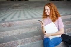 对电话和微笑负的愉快的年轻红头发人女孩,坐台阶户外 库存照片