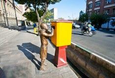 对男孩的原始的纪念碑,送信到在城市街道上的邮箱 库存照片