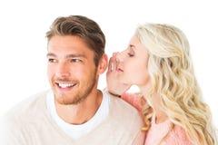 对男朋友的有吸引力的白肤金发的耳语的秘密 免版税库存照片