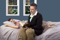 读对病的女儿 免版税库存照片