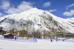 对的上升的传送带初学者为孩子和父母运行滑雪胜地的与山在背景中 库存图片