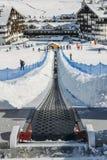 对的上升的传送带初学者为孩子和父母运行滑雪胜地的与山在背景中 图库摄影