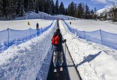 对的上升的传送带初学者为孩子和父母运行滑雪胜地的与山在背景中 免版税库存照片