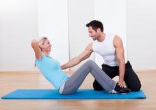 健身辅导员教的仰卧起坐 免版税库存照片
