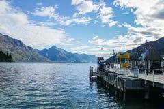 对码头的木走道有山脉的客船的在蓝天背景在新西兰 免版税库存照片