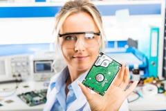 对硬盘驱动器负的年轻女性电子工程师手中 免版税库存照片