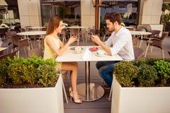 对社会网的瘾 年轻夫妇繁忙在电话,当坐在咖啡馆户外时 大阳台是好和轻的,现代,与 库存照片