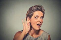对秘密地听耳朵的姿态的惊奇的年轻香的妇女手 免版税图库摄影