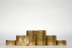 对称地增加高度的六堆硬币在白色背景,在俄国人10卢布c边缘的被布满痘痕的立场 库存照片