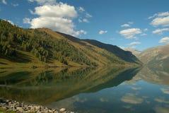 对称山在有一朵美丽的蓝天和蓬松云彩的湖反射了 免版税图库摄影
