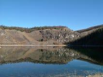 对称山在有一朵美丽的蓝天和蓬松云彩的湖反射了 图库摄影