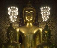 对称布局三bhuddas雕塑和两chaindelier与embross金黄油漆墙壁 图库摄影