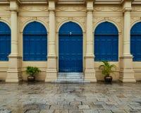 对称蓝色门在雨中 免版税库存照片