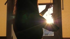 对窗口关闭的少妇步行在城市日落的帷幕 影视素材