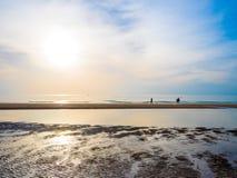 对站立在海滩的愉快的家庭的回击在日落微明时间 友好的家庭的概念 编辑的拷贝空间 免版税库存图片