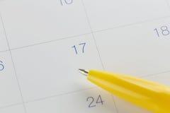 对第17的黄色笔尖在日历背景 库存照片