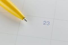 对第23的黄色笔尖在日历背景 免版税库存照片