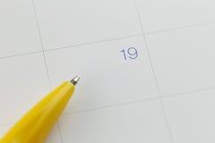 对第19的黄色笔尖在日历背景 免版税库存图片