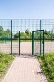 对篱芭操场和被焊接的小门的入口  库存图片