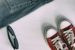 对红色运动鞋,减速火箭的片段牛仔裤,黑太阳镜 免版税图库摄影