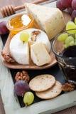 对红色酒乳酪,新鲜的葡萄,薄脆饼干的被分类的开胃菜 免版税库存图片