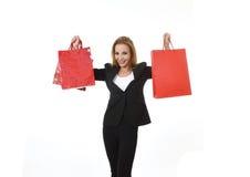 对红色购物袋微笑负的可爱的白肤金发的女实业家愉快和满意在销售概念 免版税库存图片