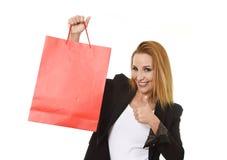 对红色购物袋微笑负的可爱的白肤金发的女实业家愉快和满意在销售概念 库存照片
