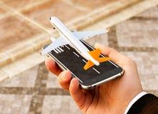 对网上搜索,买和预定飞行的智能手机申请在互联网上 免版税图库摄影