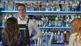 对美丽的妇女的英俊的侍酒者服务鸡尾酒一个优等的酒吧的 库存图片