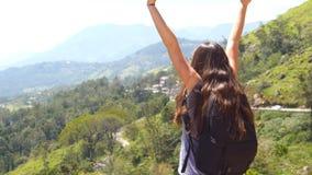 对美丽的峡谷和凯旋伸出的胳膊边缘的妇女旅游赛跑  年轻女性徒步旅行者与 股票录像