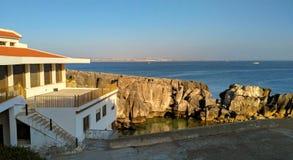 对老房子的看法在海洋附近的峭壁的日落光的, Peniche 免版税库存图片