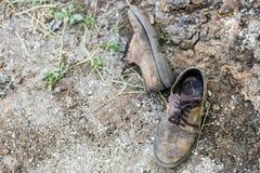 对老肮脏的使用的鞋子 放置在尘土的被放弃的被放弃的起动在地面 贫穷或卑鄙概念 Copyspace 免版税库存照片