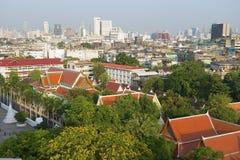 对老镇的地平线的看法有寺庙和摩天大楼的在日出的背景的从金黄山在曼谷, 库存照片