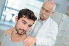 对肩膀按摩做的生理治疗师患者 免版税库存图片