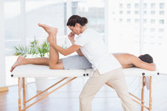对腿按摩做的生理治疗师她的患者 库存图片