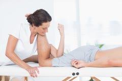 对腿按摩做的生理治疗师她的患者 库存照片